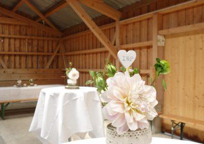 Dahlien, Spitzenbänder, Holzuntersetzer, Kerzen und die Initialen der Brautleute auf Herzen sind die Akteure der Dekoration