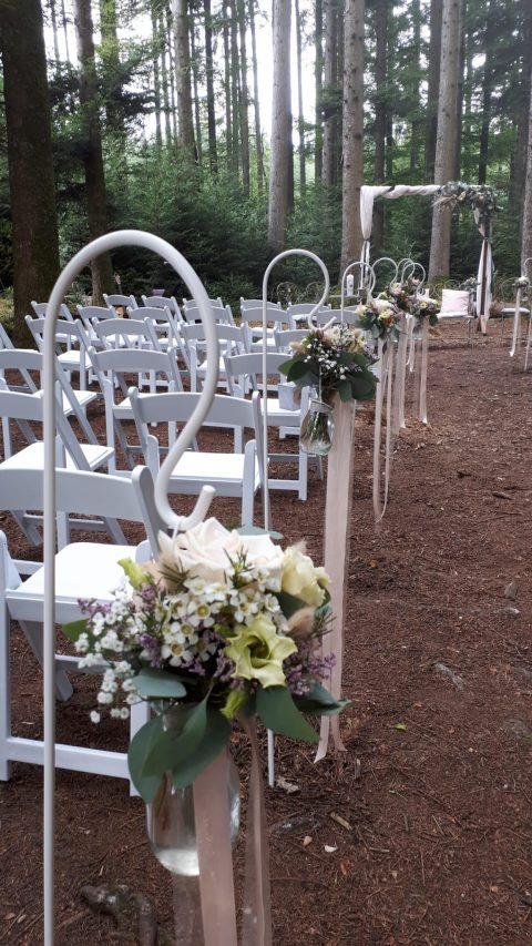 Weisse Stühle mit bequemen Sitzkissen, hübsche Blumensträusse mit Bändern und ein Traubogen im Boho-Stil erwarten die Gäste im Wald