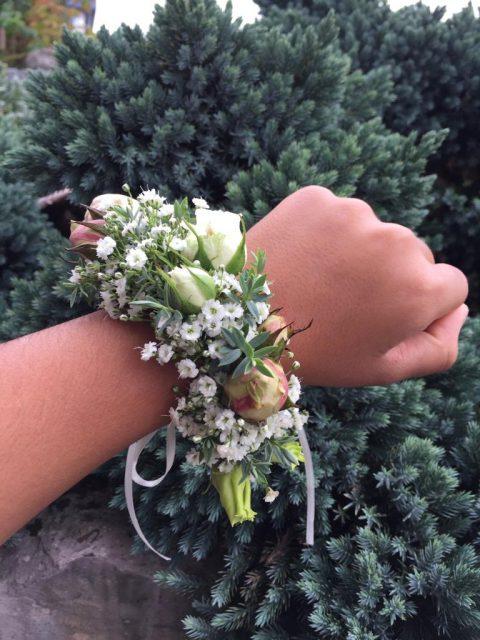 Ein zartes Blumenband schmückt das Handgelenk