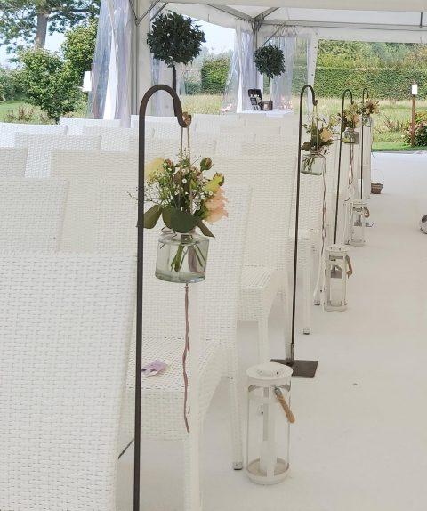 Die Trauung findet im luftigen Zelt statt - kleine Blumensträusschen und Windlichter säumen den Weg
