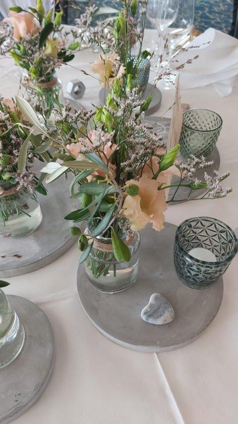 Beton, Blumen, Herzen und Teelichter zieren die Tischdekoration