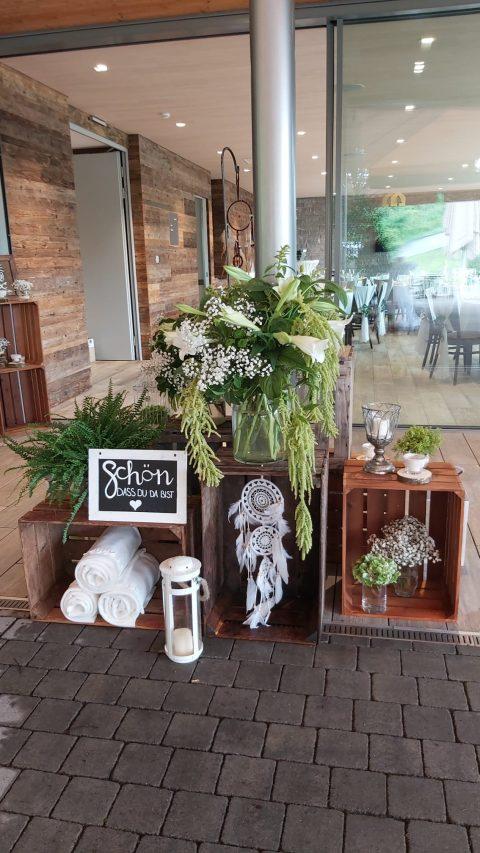 Weisse Blumen, viel Grün, Kerzen und ein Traumfänger heissen die Gäste willkommen