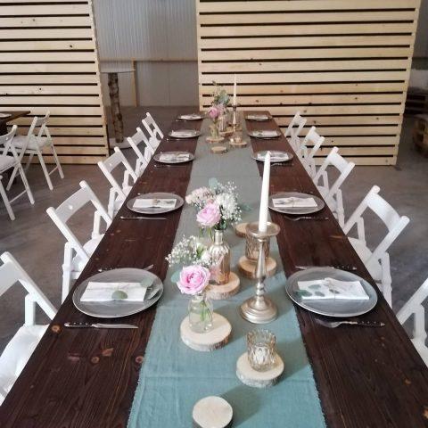 Blumensträusschen, elegante Kerzen und Holzscheiben unterstreichen den rustikal-festlichen Look dieser Hochzeit